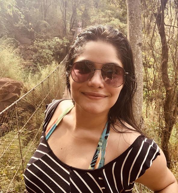 mulher de oculos escuro em uma ponte