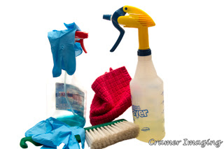Cramer Imaging's photograph of cleaning chemicals in spray bottles, disposable blue gloves, a red rag, and a duster