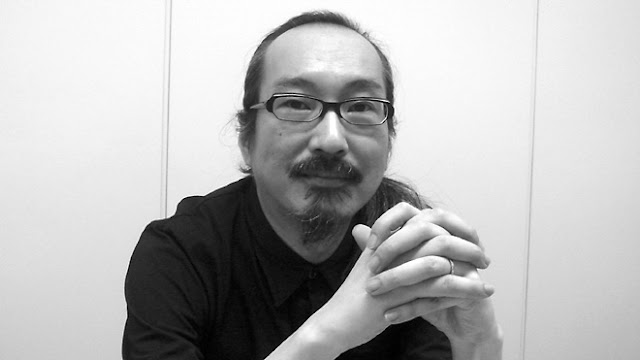 Black and white image of the late Satoshi Kon wearing glasses and pony with his hands crossed while looking at the camera