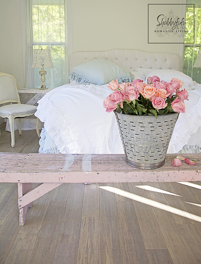 romantic room designs - peach and pink roses in a silver tin garden bucket sit on a pink vintage bench complement the white bed linens