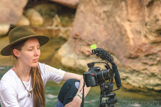 Photograph of landscape photographer Audrey Cramer checking the back of her camera on a photo shoot