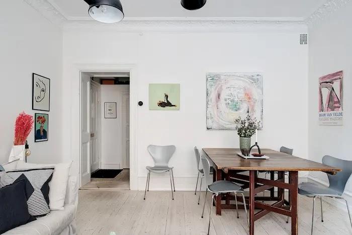 Mesa de comedor con gran capacidad adosada a la pared en un salón pequeño