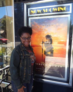 Jenee Darden posing with Wonder Woman poster after watching the movie.