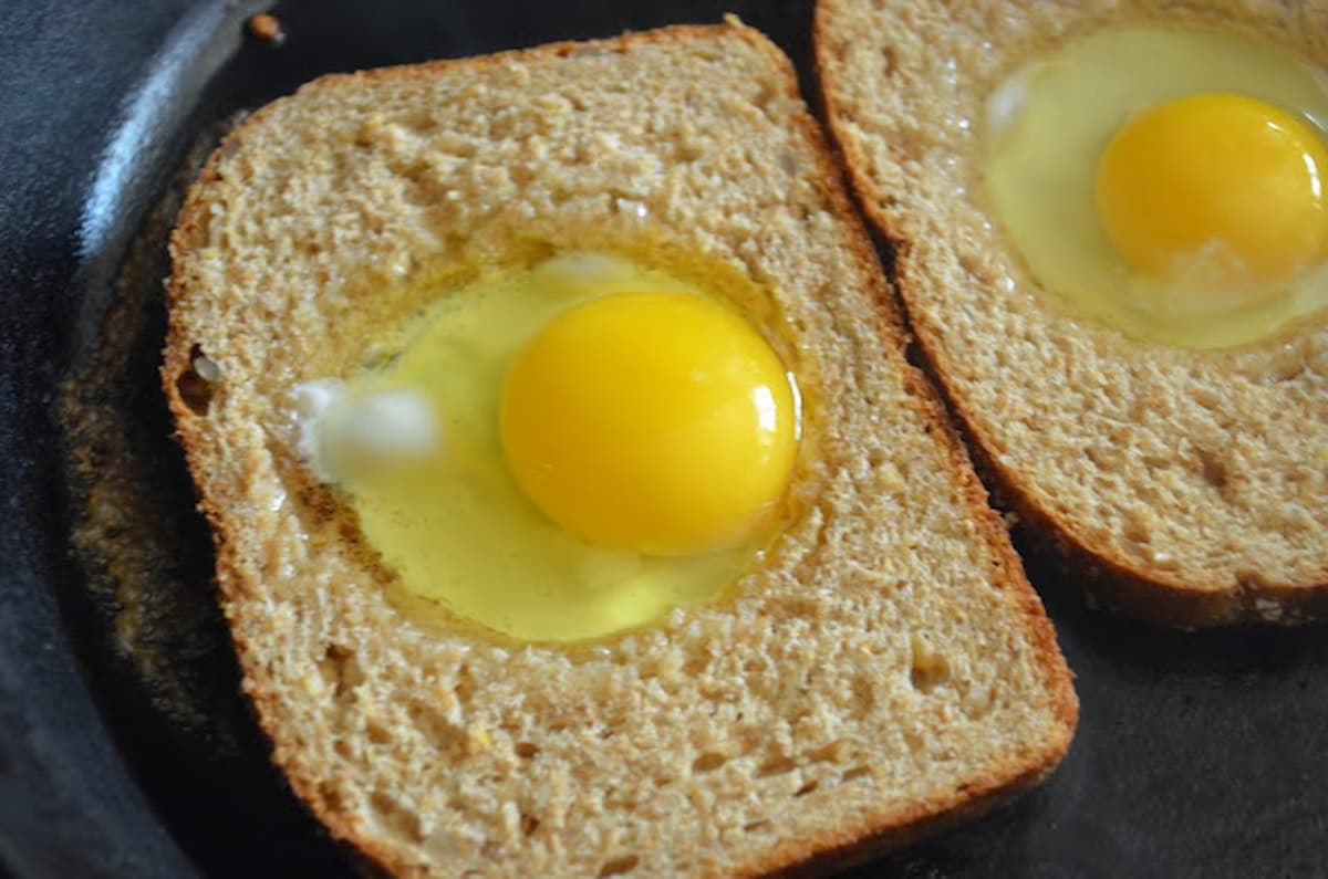 2 Pieces of Bread with a circle cut out in the center with Eggs placed in the center in a cast iron skillet.