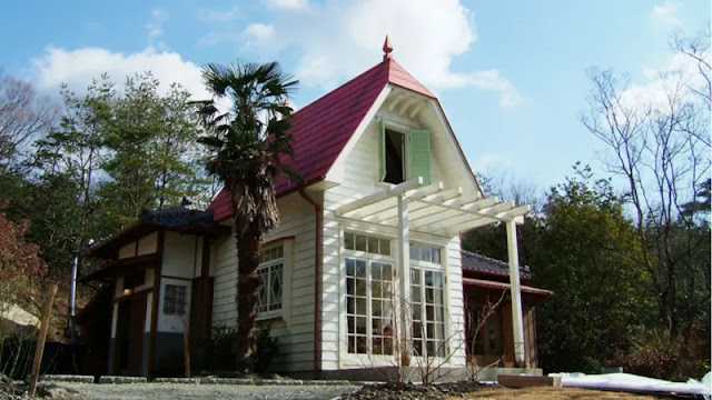 A white house with red roof beside trees in japan