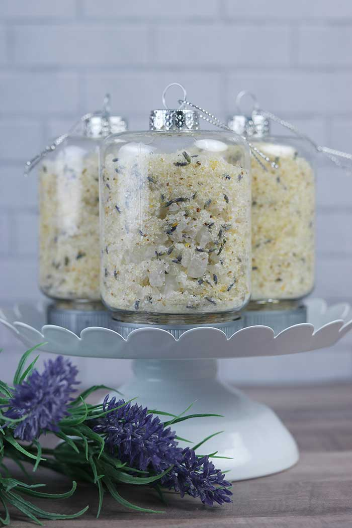 How to make an easy lemon lavender bath salts recipe with essential oils. These use aromatherapy to promote calming and stress relief and other benefits.  They are easy to make with Epsom salt, sea salt, essential oils, lavender, and dried citrus peels. This makes a great Christmas DIY gift with cute container ideas with tiny mason jar ornaments for containers. Give the gift of homemade relaxing detox herbal bath salts for Christmas. #bathsalts #diy #gift #lemon #lavender