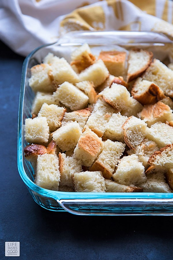 Cubed bread crumbs in glass baking dish for Overnight French Toast Casserole