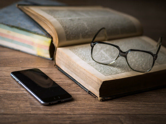 Glasses on a book next to a cellphone.