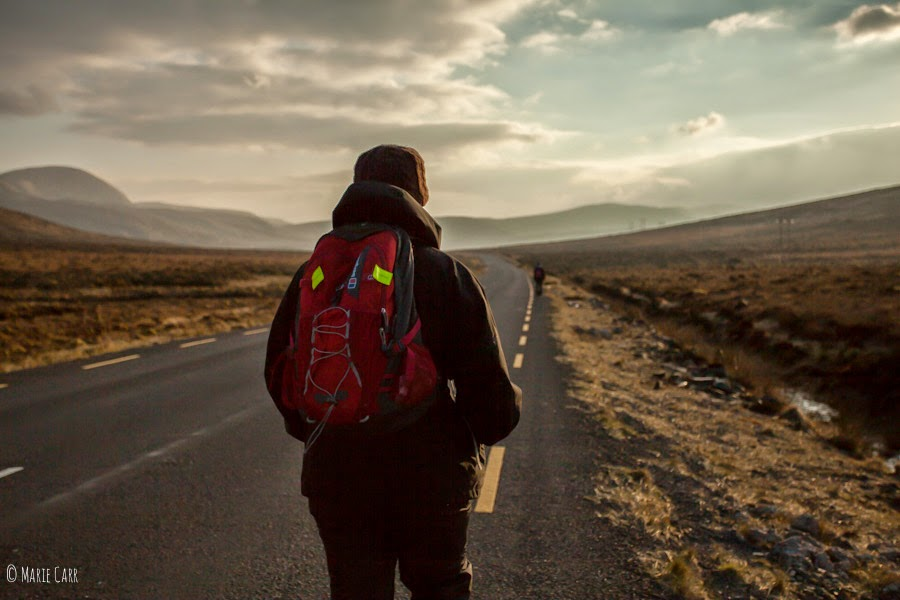Hiker carrying a red backpack walking along a main road in Co. Donegal, Ireland