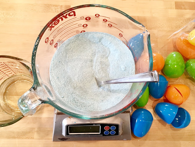 Weighing ingredients for making bath bombs using plastic Easter eggs as bath bomb molds.