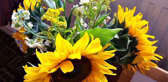 A vase with sunflowers and other random flowers in