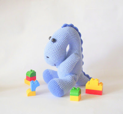 Colorful crochet amigurumi dinosaur playing with blocks