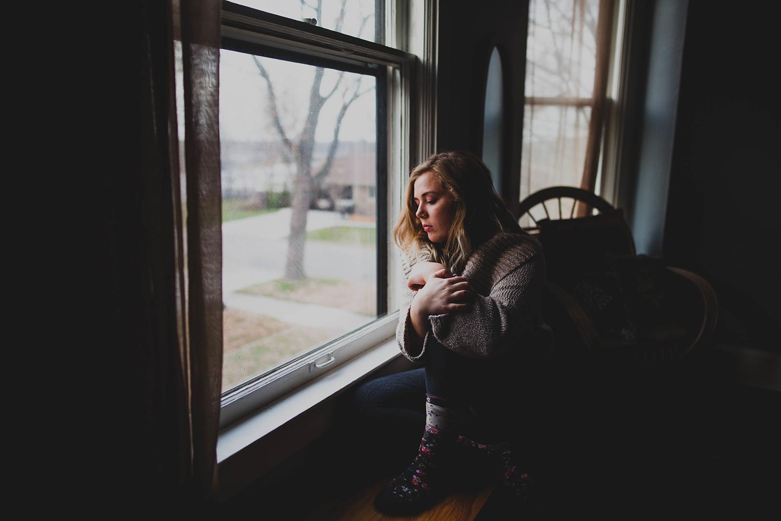 garota pensativa sentada janela