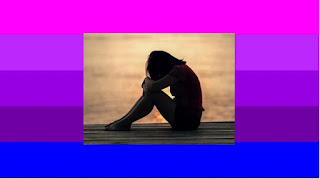 Picture of a young woman sitting down, looking sad.  Behind the picture, the flag used by some of the Transgender communities.