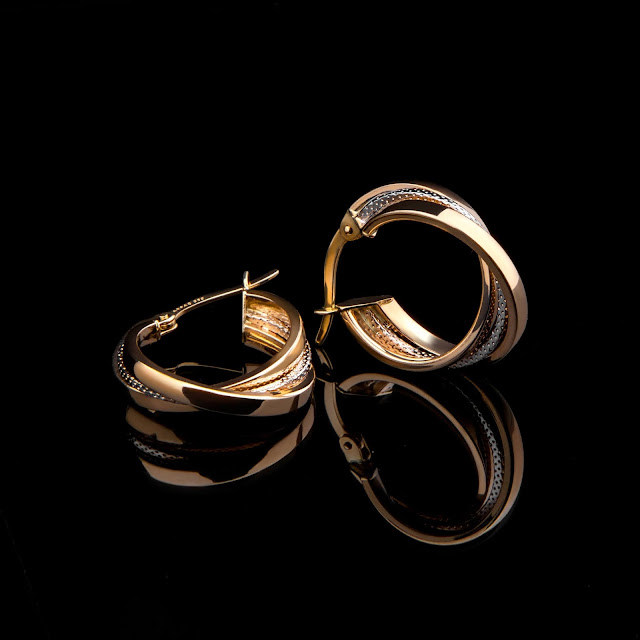 A pair of gold earrings on a black backdrop.