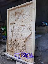 Relief gambar wayang Gatotkaca untuk hiasan tempel dinding rumah yang dibuat dari batu alam paras jogja / batu putih