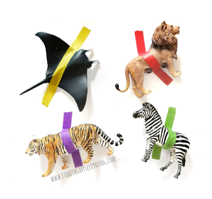 Animal figurines taped down with washi tape for a fine motor rescue activity.