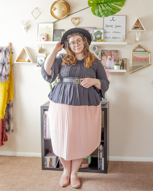 An outfit consisting of a wide brim black hat, a black Victorian inspired blouse with pleats and ruffles on the bodice, angel sleeves at the elbow and a peplum hem belted over a pink pleated midi skirt and muted pink pointed toe mules.