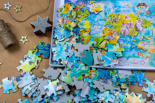 An open jigsaw box with a world map jigsaw design printed on to the inside of the box with the pieces spilling out.