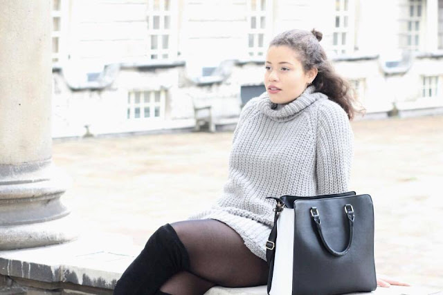 Image of Eboni sitting looking into the distance wearing a grey jumper from Missy Empire