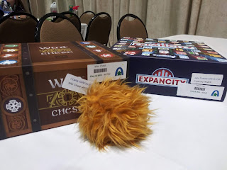 A copy of War Chest and a copy of Expancity, both with stickers on them proclaiming them to be play-to-win prizes and the names of the winners, on a table next to a toy tribble.