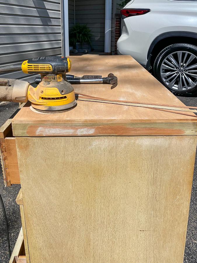 Sanding off damaged veneer