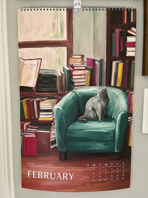 calendar page featuring a cat on a chair surrounded by books