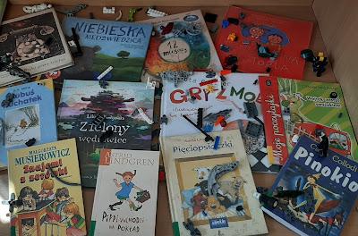 W gablocie leży 12 książek oraz części klocków Lego.