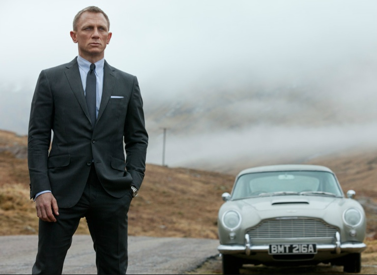 Daniel Craig as Bond standing by the side of the road next to the Aston Martin
