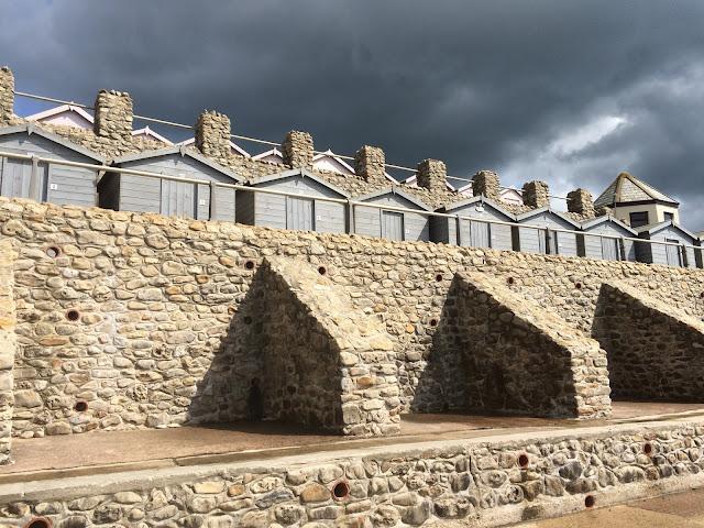 beach huts under an ominous dark cloud.