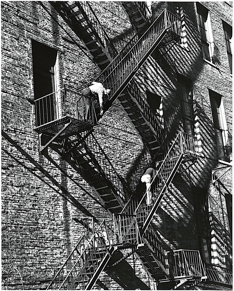 an André Kertész 1949 photograph of men working on a fire escape with long shadows