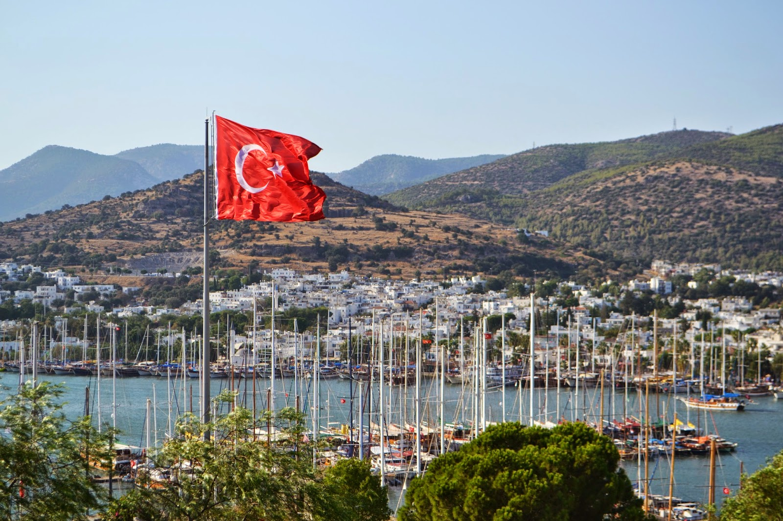 a Turkish flag can be seen in the foreground and the harbour full of boat can be seen bind this. a hill of white washed buildings can be seen in the background