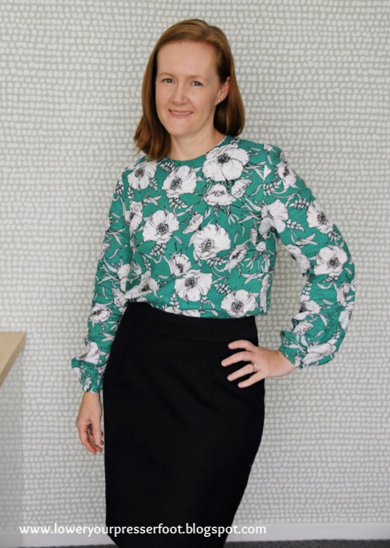 woman posing in a bright green floral top worn with a navy blue pencil skirt