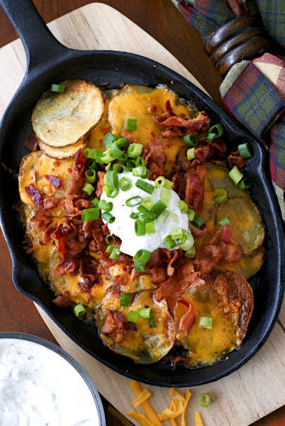 Top view of loaded potato nackos on an oval black cast iron plate.