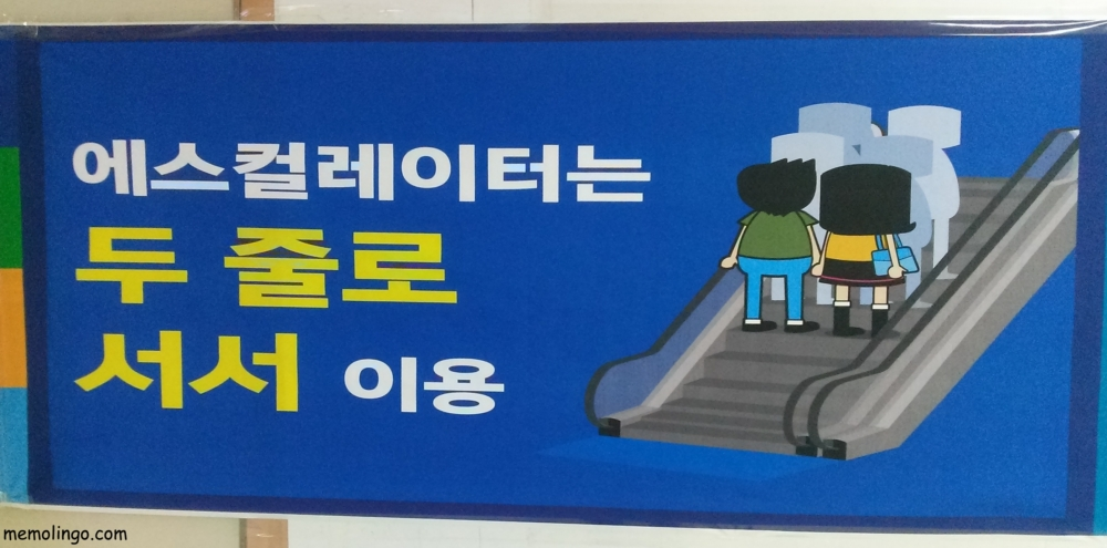 Cartel en coreano pidiendo dos filas en las escaleras mecánicas