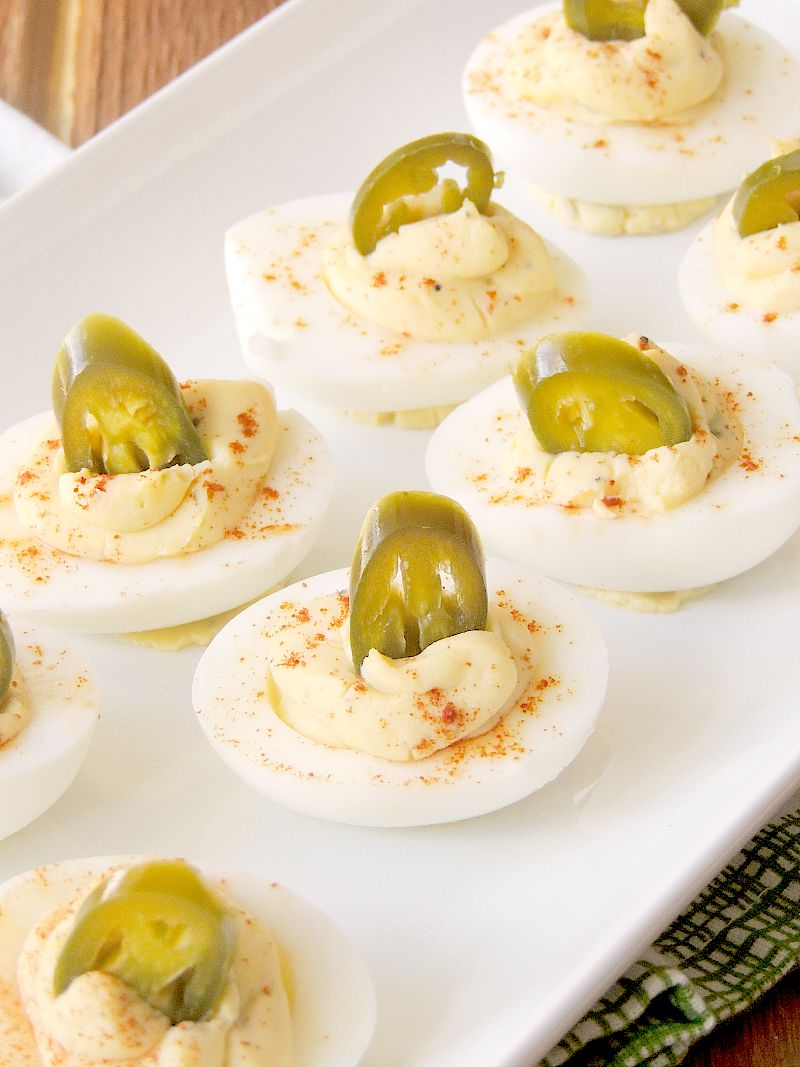 Closeup photo of Jalapeno Popper Deviled Eggs on a white serving tray.