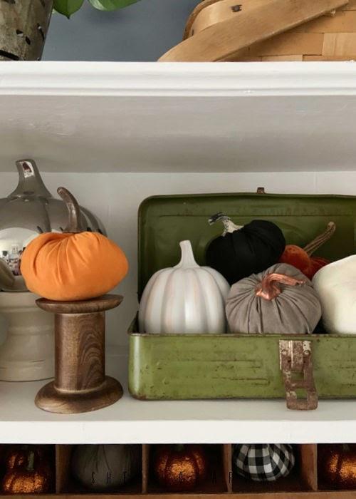 fall vignette pumpkins in a green tackle box.