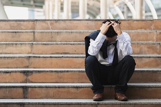 homem sentado na escadaria preocupado