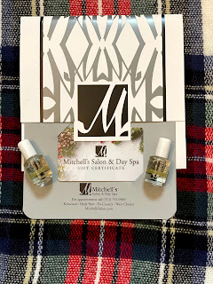 Mitchell's Salon gift card with two nail oils on a plaid background