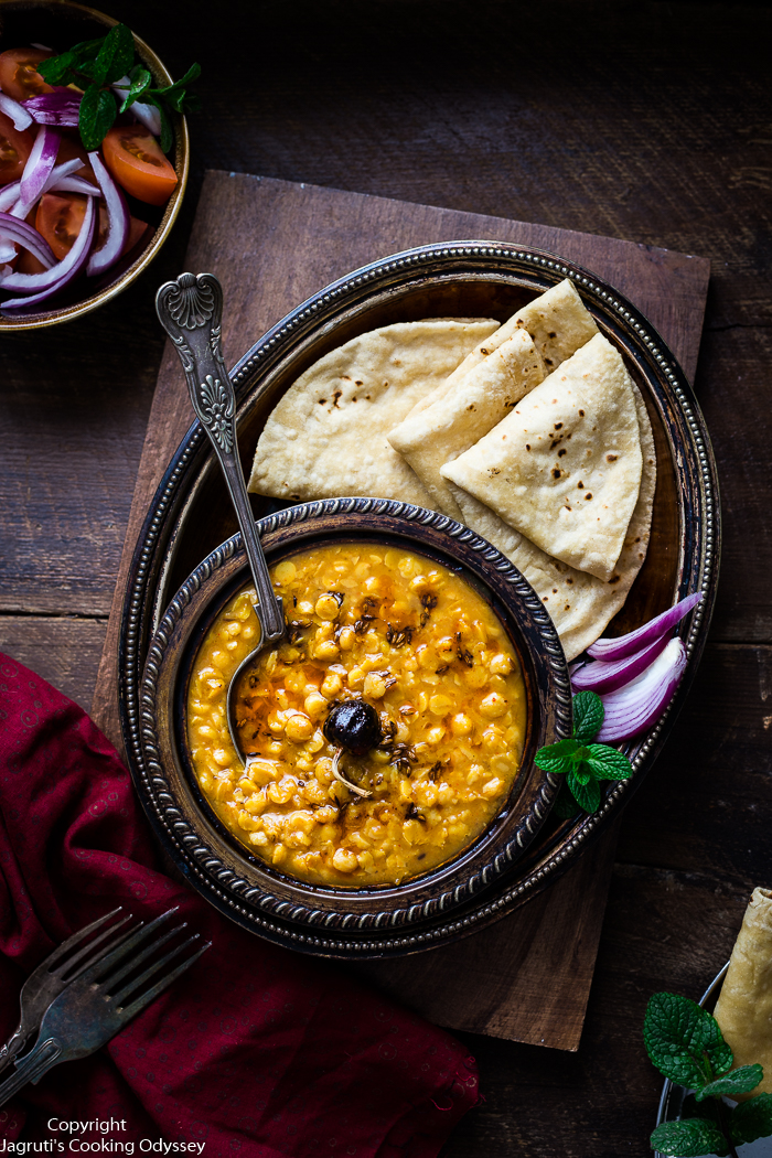 This Indian style split Bengal gram lentils cooked and served in a metal bowl with roti.