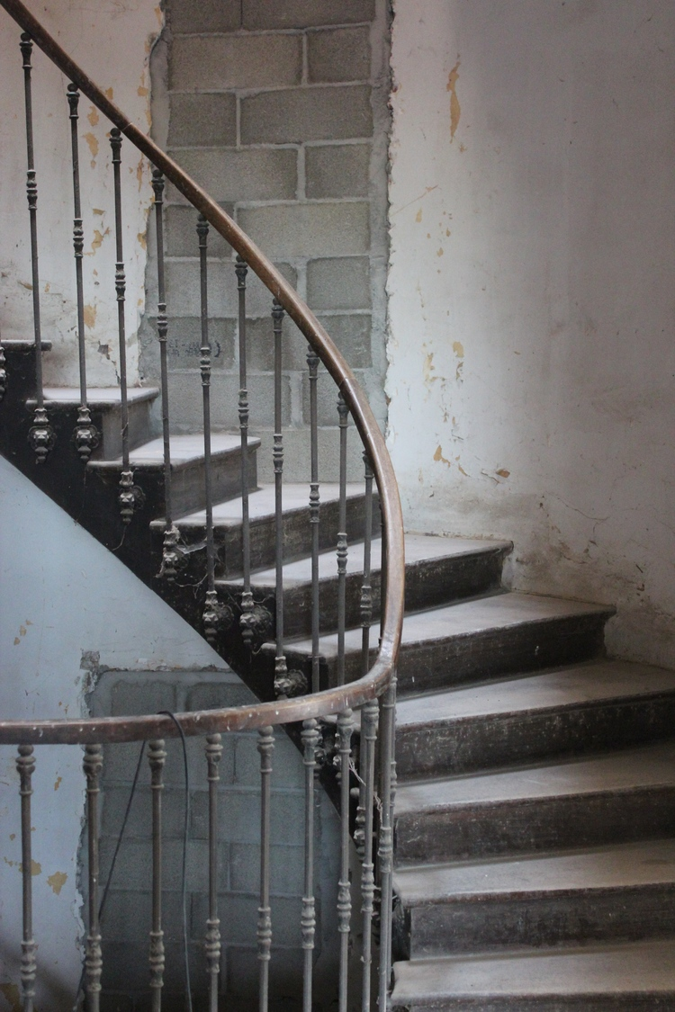 Stripped wallpaper in stairway of decaying Chateau de Gudanes