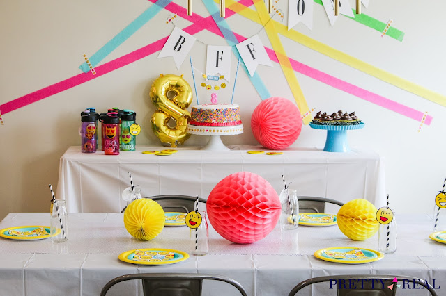 emoji party favors, honeycomb balls, emoji birthday cake, and emoji party backdrop