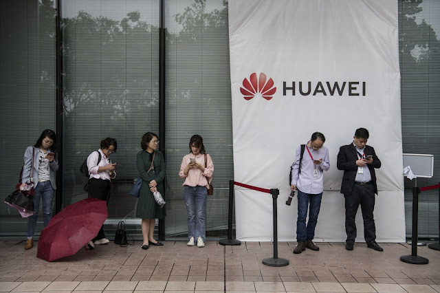 Huawei employees wait for a shuttle bus at the company's Bantian campus