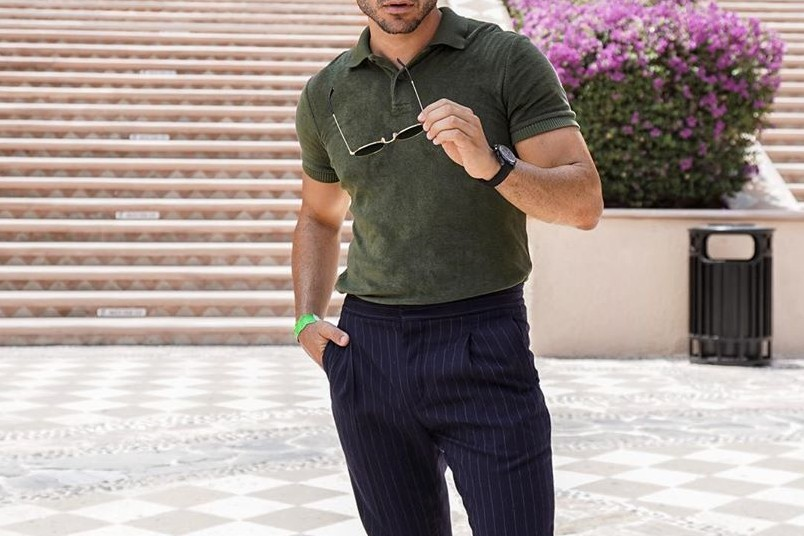 A man pair up his polo shirt with a classy watch and shades.