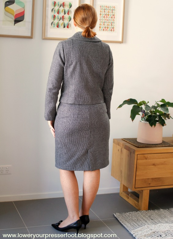 picture of a back of a lady wearing a skirt suit