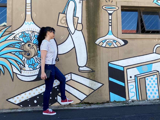 Girl poses with Brothers of Light mural in Cape Town
