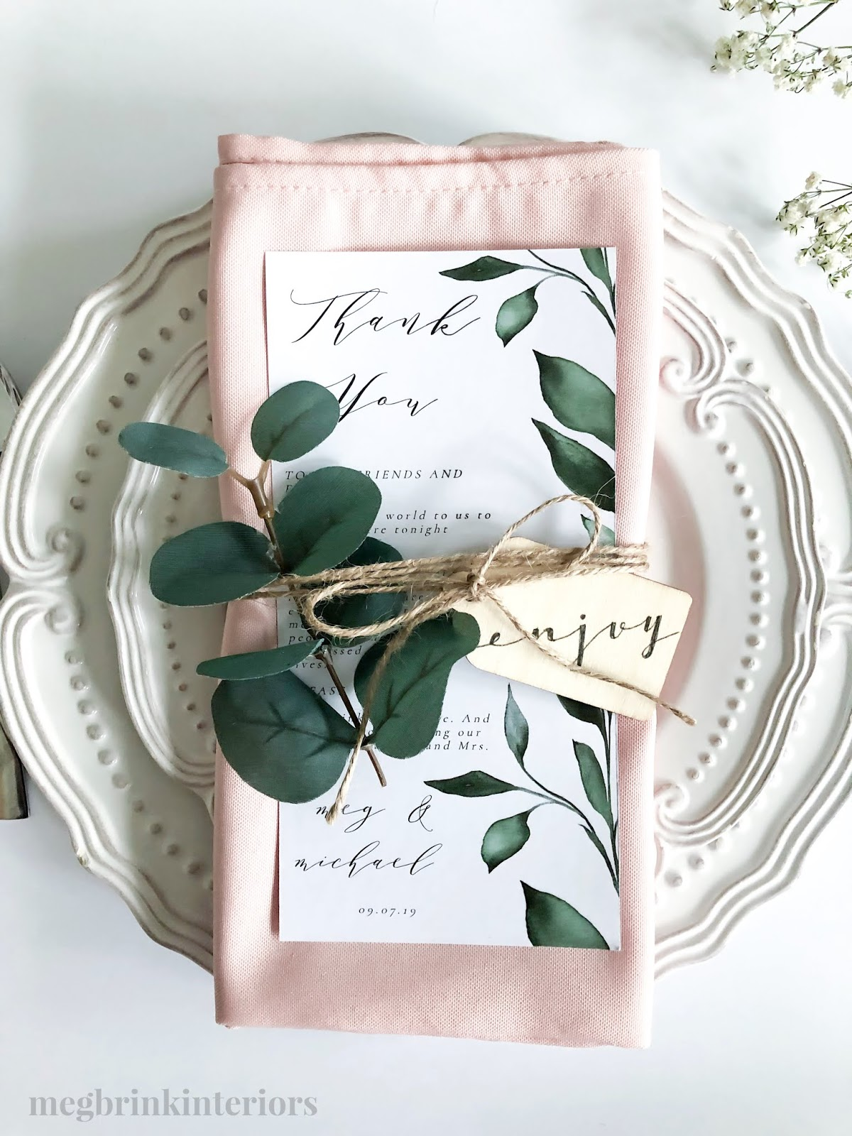 Blush pink cloth napkins with greenery, wooden tags and twine make the perfect wedding place setting!