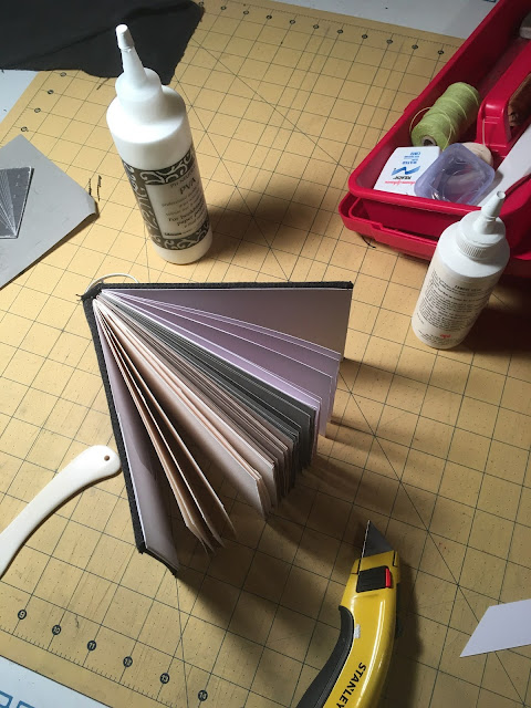 Handmade sketchbook containing white, toned tan, toned gray, and watercolor paper, with mat knife, bone folder, glue, and dental floss.