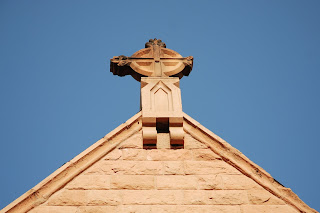 cross at the top of a peaked roof on a church
