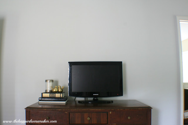 Wood dresser with TV and stack of books in front of a light gray wall